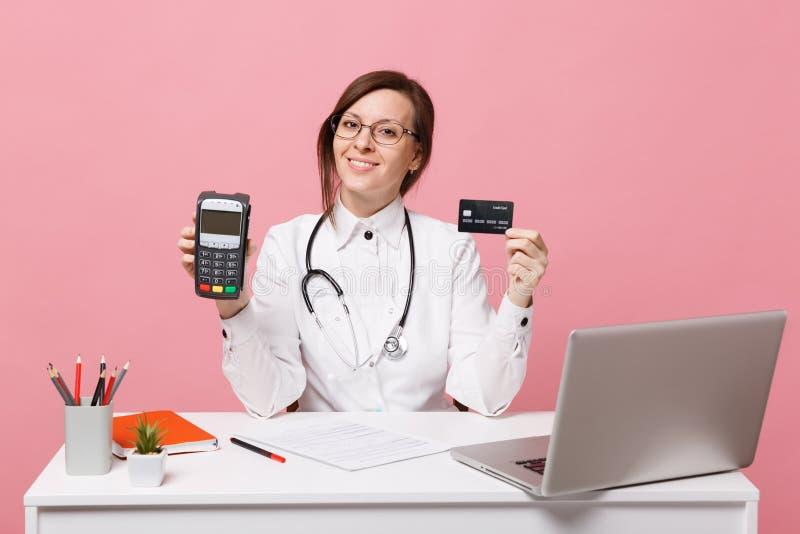 De vrouwelijke arts zit bij het bureauwerk aangaande computer met medische die documentcreditcard in het ziekenhuis op pastelkleu royalty-vrije stock foto