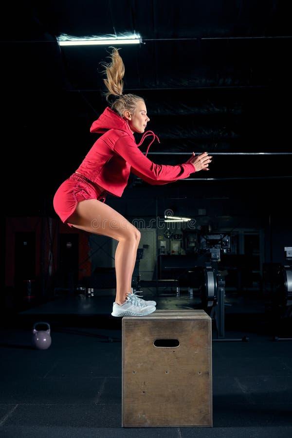 De vrouwelijke atleet voert doossprongen bij gymnastiek uit royalty-vrije stock afbeelding