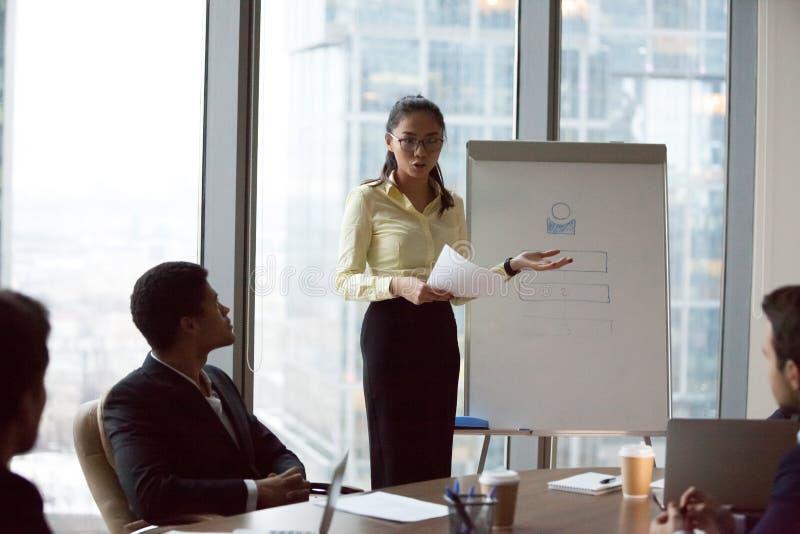 De vrouwelijke Aziatische arbeider maakt flipchart presentatie op vergadering stock afbeeldingen
