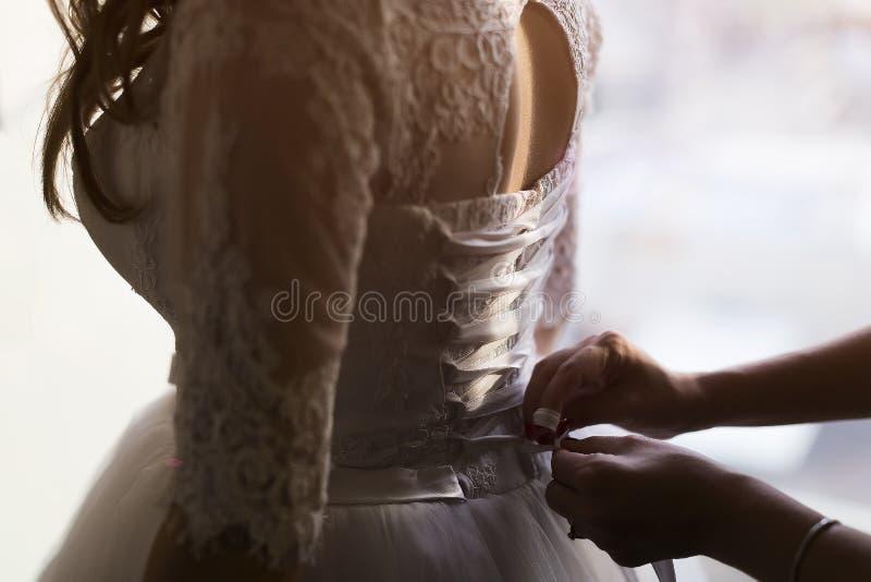 De vrouwelijke band van de handenhulp op de rug van de kleding royalty-vrije stock foto
