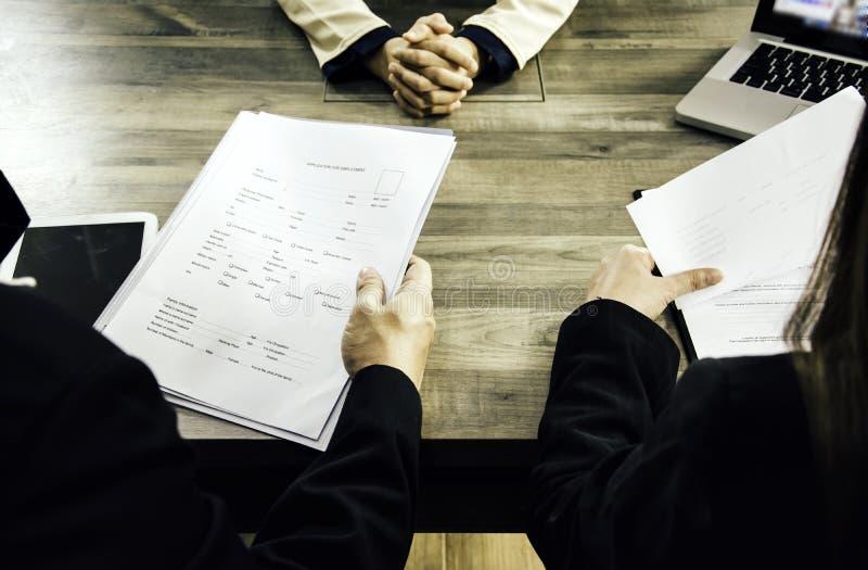 De vrouwelijke bedrijfsvrouw legt sollicitatie aan managers en commissies, rekruteringsafdelingen van voor bedrijf in gespreksrui stock foto