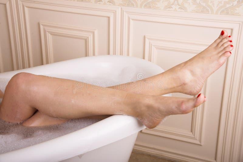 De vrouwelijke benen hingen over de badkamers stock afbeelding