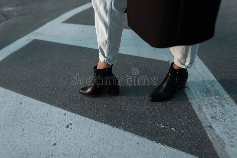De vrouwelijke benen sluiten omhoog De vrouw in een lange laag in leer zwarte laarzen in modieuze jeans loopt langs de weg in de  royalty-vrije stock fotografie