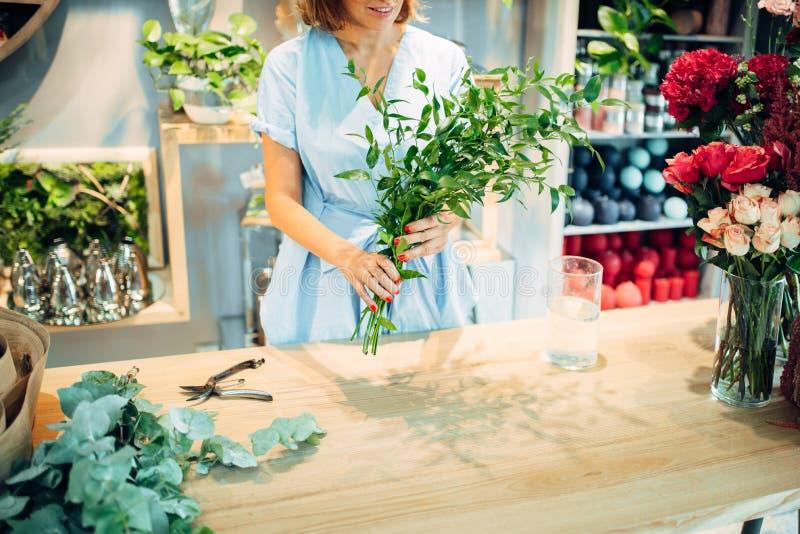 De vrouwelijke bloemist houdt verse bloemen in bloemenwinkel royalty-vrije stock foto's