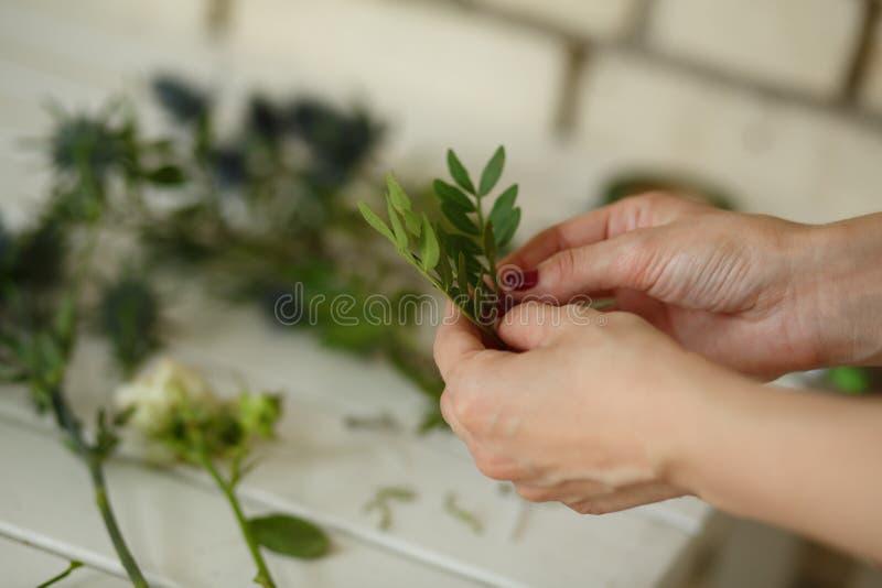 De vrouwelijke bloemist zoekt bouqet uit verse bloem voor de decoratie van de huwelijksceremonie bijeen Decoratie van gebeurtenis royalty-vrije stock fotografie