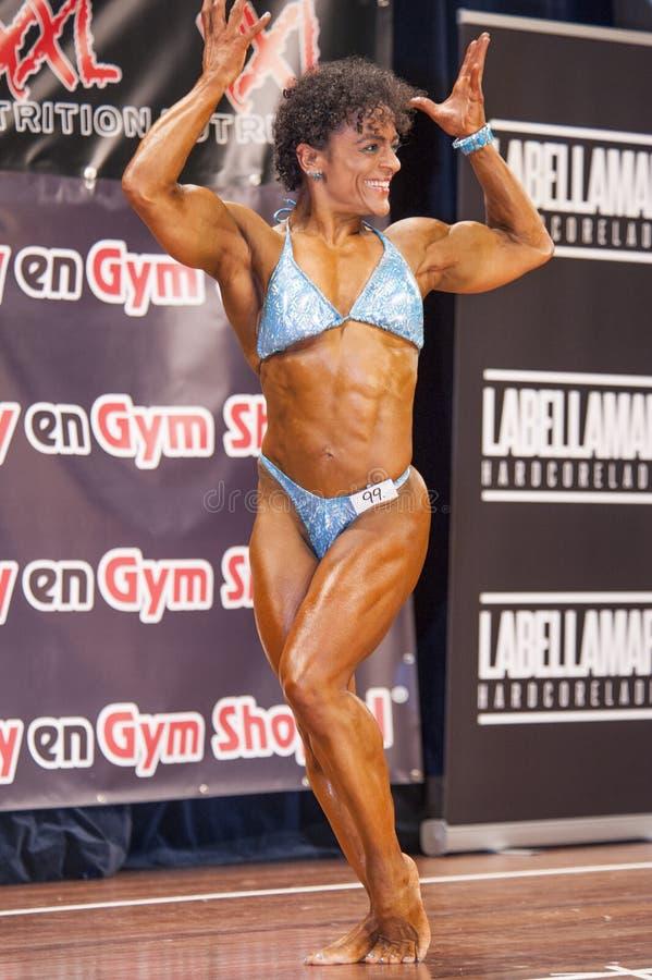 De vrouwelijke bodybuilder in dubbele bicepsen stelt en blauwe bikini stock foto's