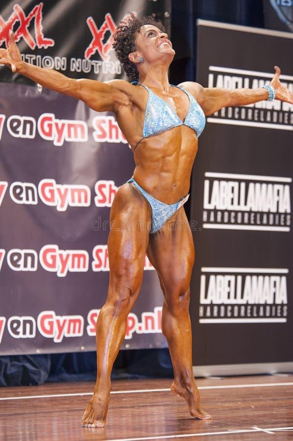 De vrouwelijke bodybuilder in gelukkig en sexy stelt en blauwe bikini stock afbeelding