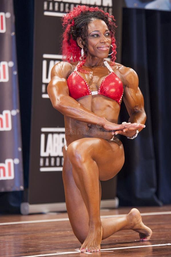 De vrouwelijke bodybuilder in rode bikini toont het grote bicepsen stock foto