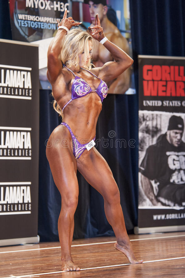 De vrouwelijke bodybuilder vooraan dubbele bicepsen stelt en doorboort bikini stock afbeeldingen