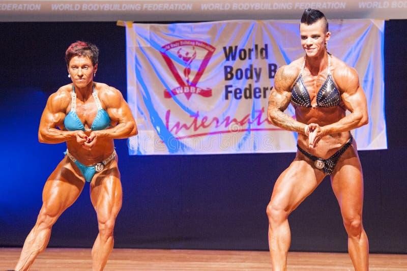 De vrouwelijke bodybuilders buigen hun spieren om hun lichaamsbouw te tonen stock afbeeldingen