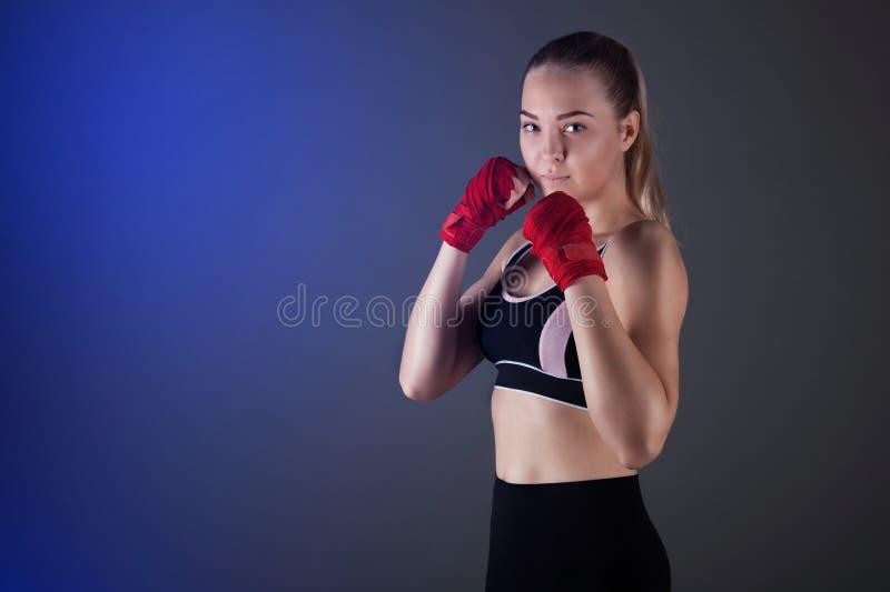 De vrouwelijke bokser maakt een strijd met een schaduw, donkere achtergrond met ruimte voor tekst Sterk en zeker stock fotografie