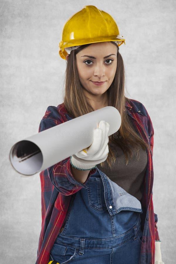 De vrouwelijke bouwvakker geeft plannen voor u royalty-vrije stock afbeeldingen