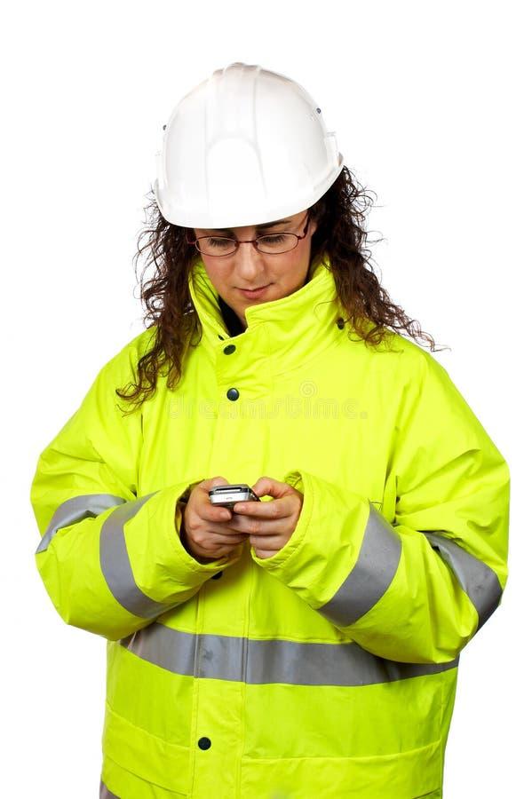 De vrouwelijke bouwvakker verzendt een SMS stock afbeeldingen