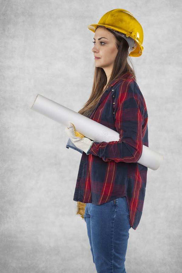 De vrouwelijke bouwvakkerholding plant dichtbij royalty-vrije stock foto's