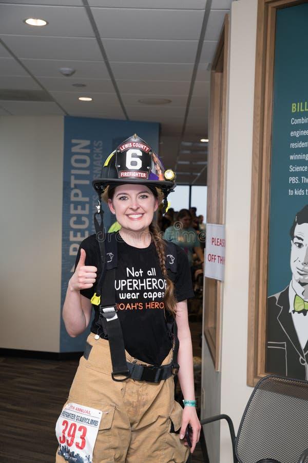 De vrouwelijke brandbestrijder die trede voltooien beklimt gebeurtenis stock foto