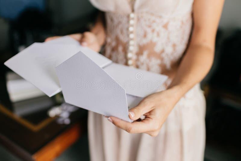 De vrouwelijke bruid in witte kleding, houdt witte brief of de envelop, treft voor uitnodiging voorbereidingen, voorbereidingen t royalty-vrije stock foto's