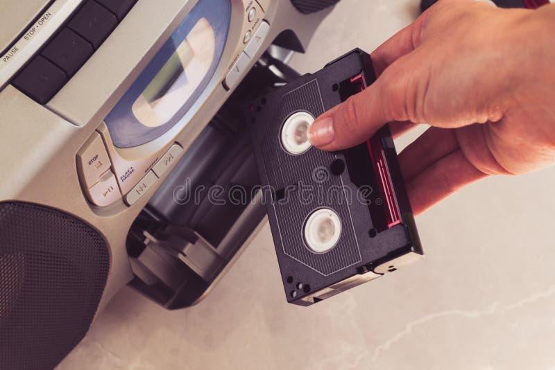 De vrouwelijke cassette van handentussenvoegsels in audiorack royalty-vrije stock foto's