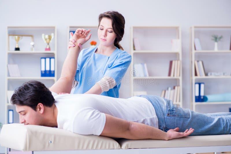 De vrouwelijke chiropracticus arts die mannelijke patiënt masseren stock foto