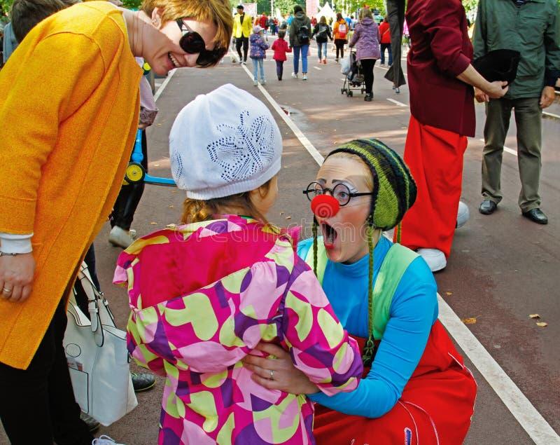 De vrouwelijke clown onderhoudt het kind bij festival ` Clownfest ` in het park Sokolniki in Moskou royalty-vrije stock afbeelding