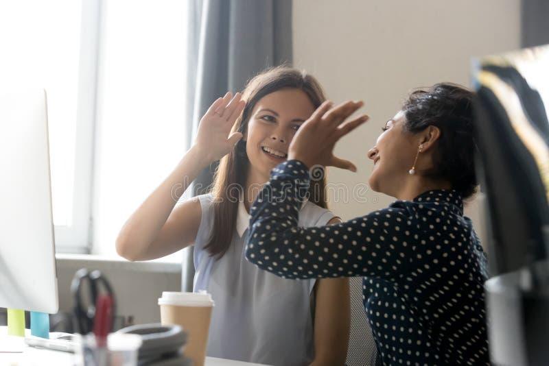 De vrouwelijke collega's vieren bedrijfswinst, die vijf geven stock fotografie
