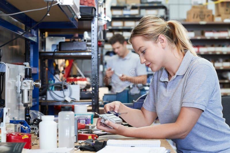De vrouwelijke Component van Ingenieursin factory measuring bij het Werkbank Usi stock fotografie