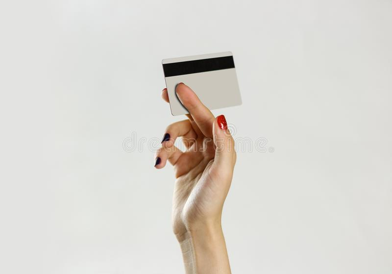 De vrouwelijke creditcard van de handholding Geïsoleerdu op grijze achtergrond Cl royalty-vrije stock afbeelding