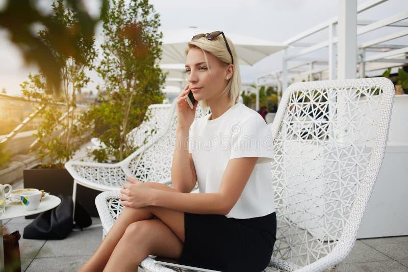 De vrouwelijke deskundige advocaat roept via celtelefoon, terwijl in koffie zit stock foto