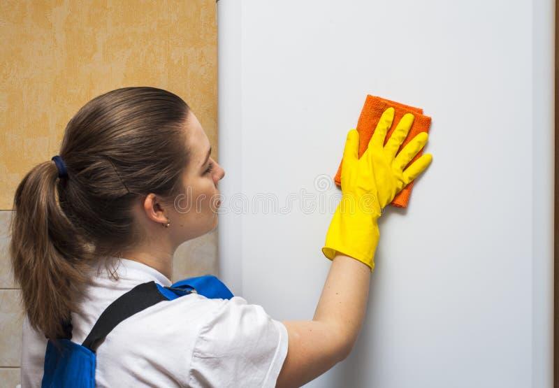 De vrouwelijke deur van de portier schoonmakende ijskast met vod stock afbeeldingen