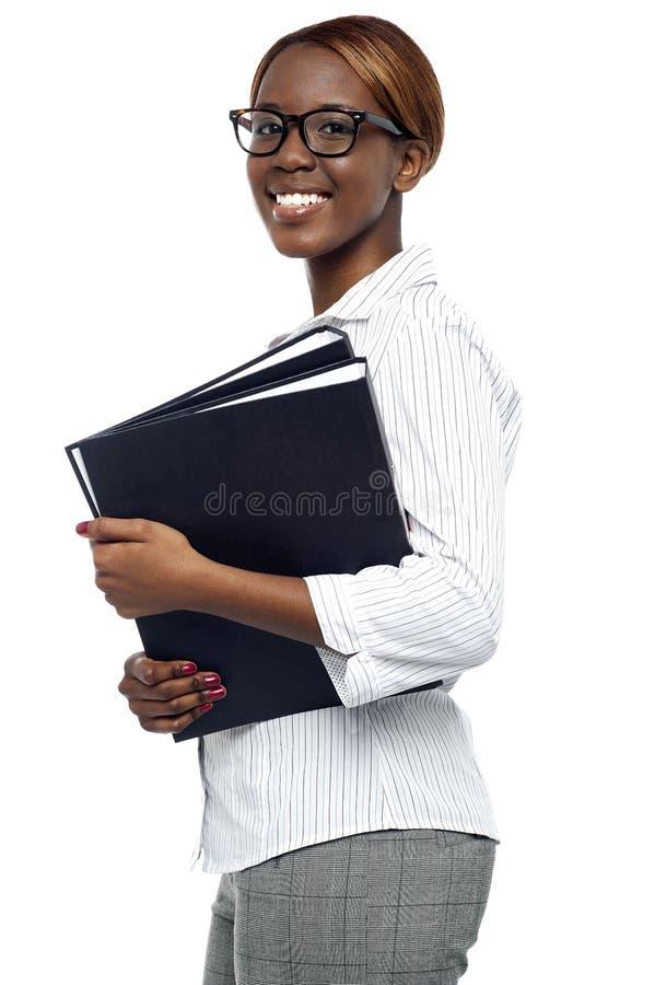 De vrouwelijke dossiers van het secretaresse dragende bureau stock foto