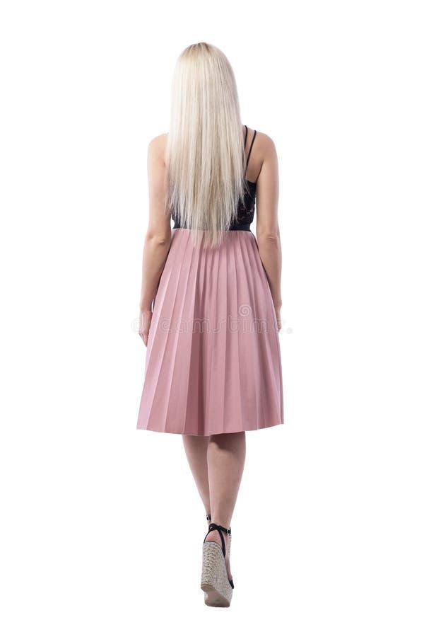 De vrouwelijke elegante jonge vrouw die van het blonde rechte haar in roze rok elegant weggaan royalty-vrije stock afbeelding