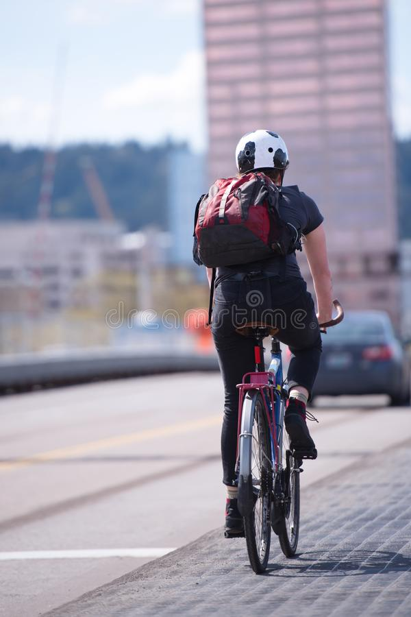 De vrouwelijke fietser met rugzak cirkelt langs fietspad stock afbeelding