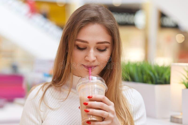 De vrouwelijke foto van het charmeren van blonde drinkt cocktail, stelt in koffie, draagt witte toevallige sweater, heeft rode ma royalty-vrije stock afbeelding