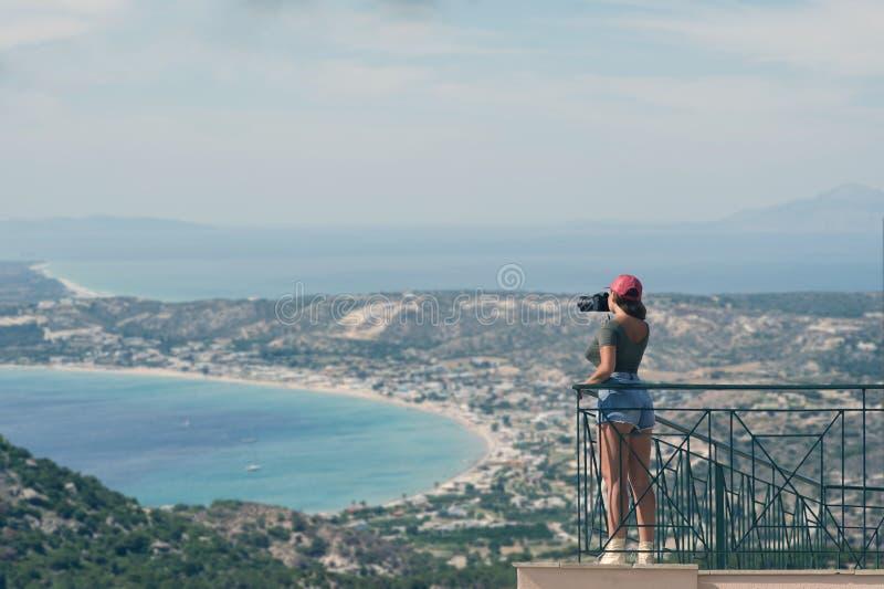 De vrouwelijke fotograaf in een rood GLB met een camera bevindt zich op het balkon tegenovergesteld van de Griekse stad van Volos royalty-vrije stock foto's