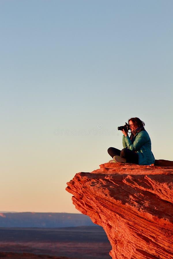 De vrouwelijke fotograaf neemt beelden met grote camerazitting op de rand van de klip bij Hoefijzerkromming stock foto's