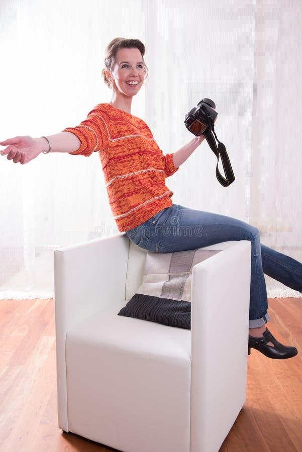 De vrouwelijke Fotograaf toont het stellen op stoel stock foto's