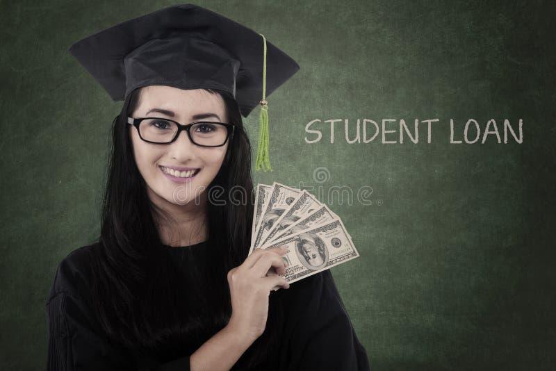De vrouwelijke gediplomeerde student krijgt geld voor lening royalty-vrije stock foto