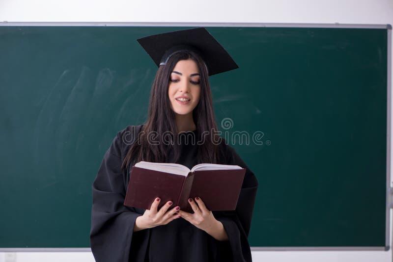 De vrouwelijke gediplomeerde student voor groene raad stock foto