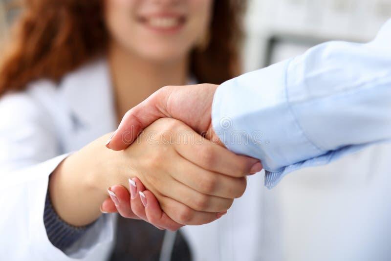 De vrouwelijke geneeskunde hand van de artsenschok zoals hello met onderneemster royalty-vrije stock afbeeldingen
