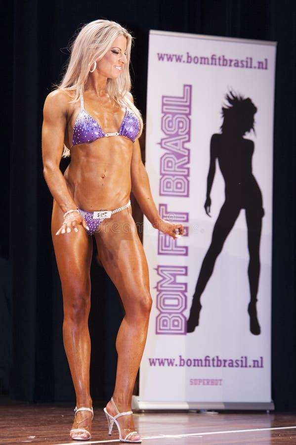 De vrouwelijke glimlachen van de bodyfitnessmededinger op stadium royalty-vrije stock foto