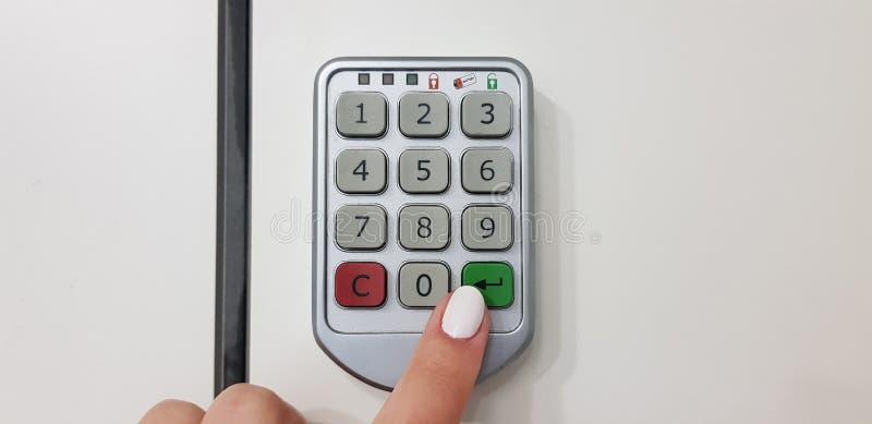 De vrouwelijke groene vingerduwen gaan sleutel op een deur van veiligheids witte kast in royalty-vrije stock afbeelding