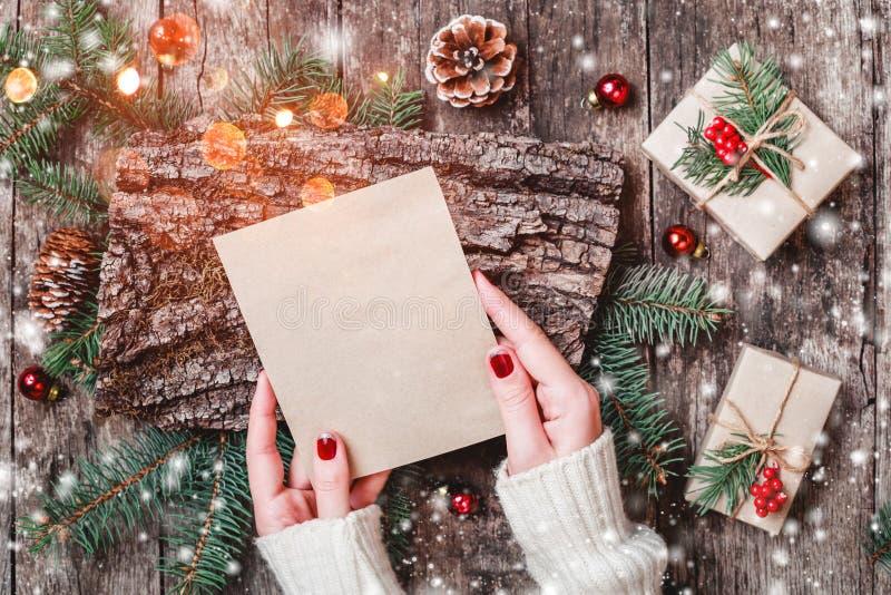 De vrouwelijke hand die een brief schrijven aan Kerstman op houten achtergrond met Kerstmisgiften, schorstextuur, Spar vertakt zi royalty-vrije stock afbeelding