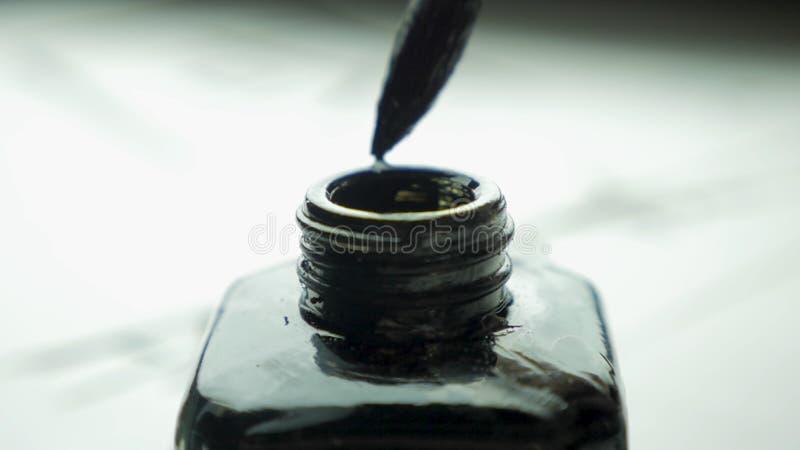 De vrouwelijke hand dompelt borstel in een kruik inkt voor tekenings dichte omhooggaand onder Chinese Ouderwetse Verfborstels met stock afbeeldingen