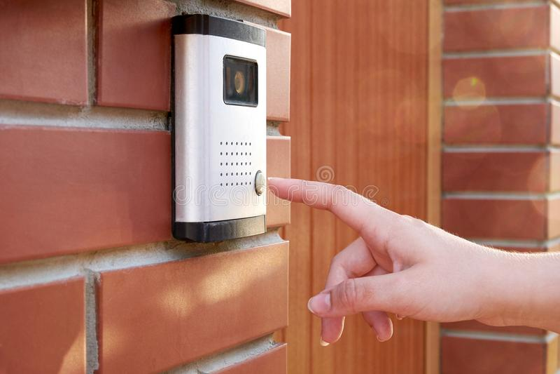De vrouwelijke hand drukt een knoopdeurbel met intercom stock afbeelding