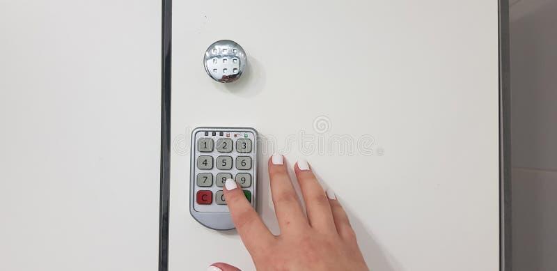 De vrouwelijke hand duwt op een aantalsleutel op elektrisch veiligheidsslot royalty-vrije stock fotografie