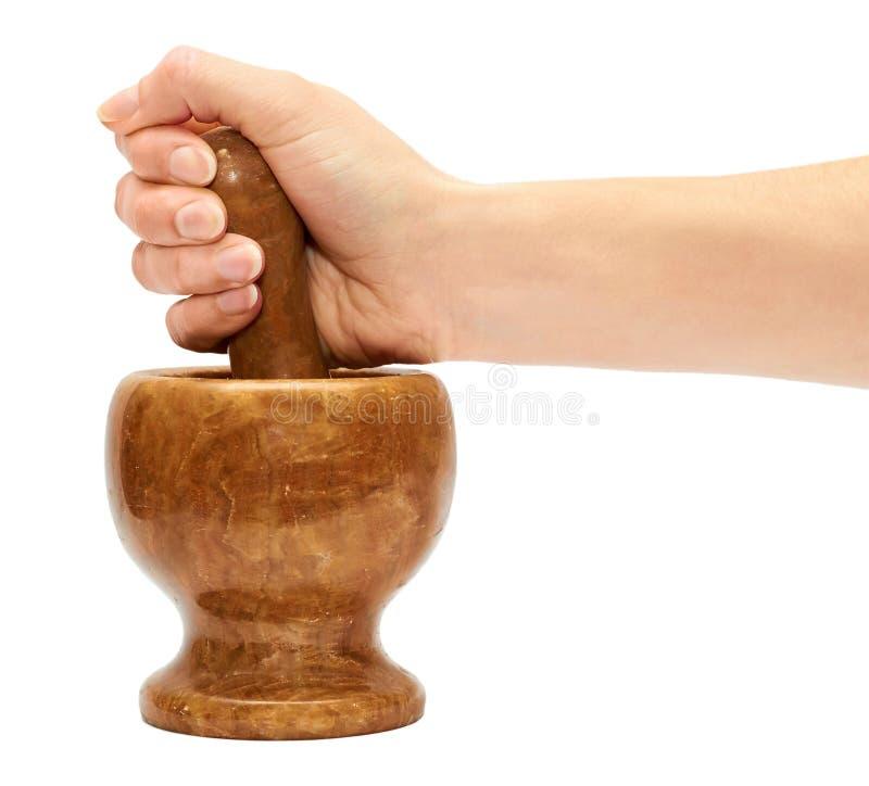 De vrouwelijke hand gebruikt een steenmortier om kruiden voor te bereiden stock foto