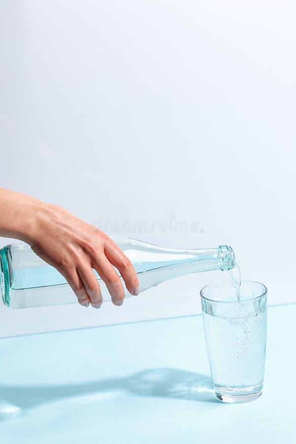 De vrouwelijke hand giet zuiver mineraalwater van een fles in een glas Minimalistisch ontwerp Het concept het gezonde eten stock afbeelding