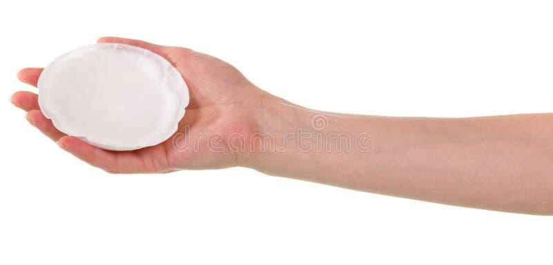 De vrouwelijke hand houdt een absorberend die damesslipje voor borsten op whi worden geïsoleerd royalty-vrije stock afbeeldingen