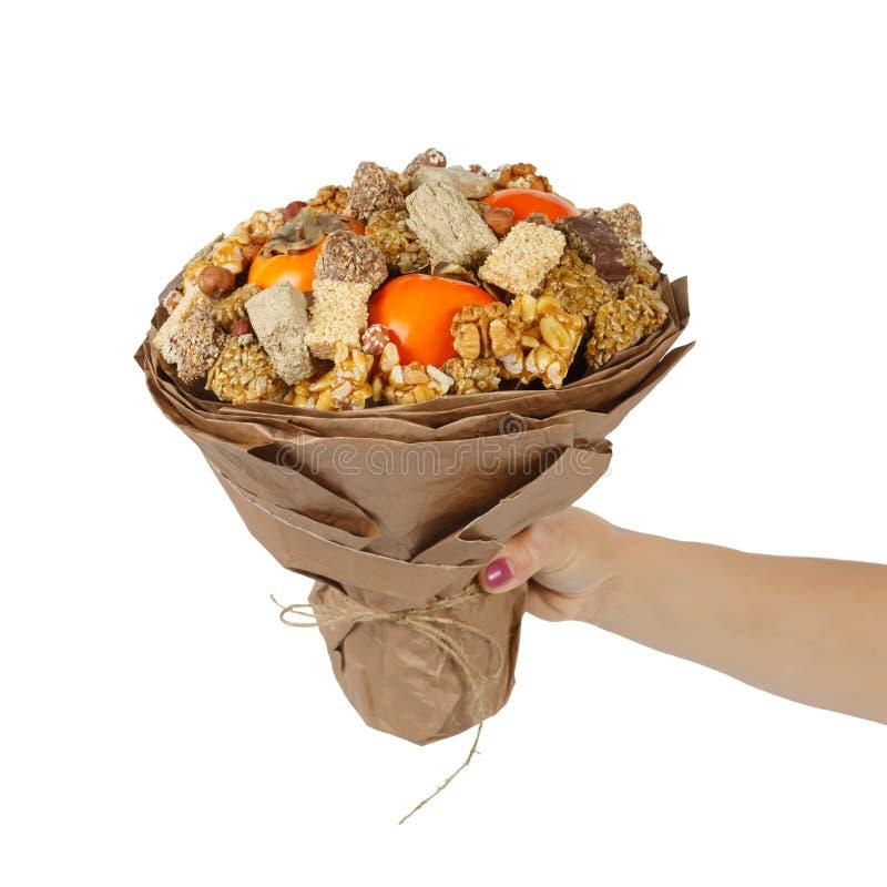 De vrouwelijke hand houdt een origineel boeket bestaand uit oosterse snoepjes - halva, sesambreuken, noten, chocolade en dadelpru royalty-vrije stock afbeelding