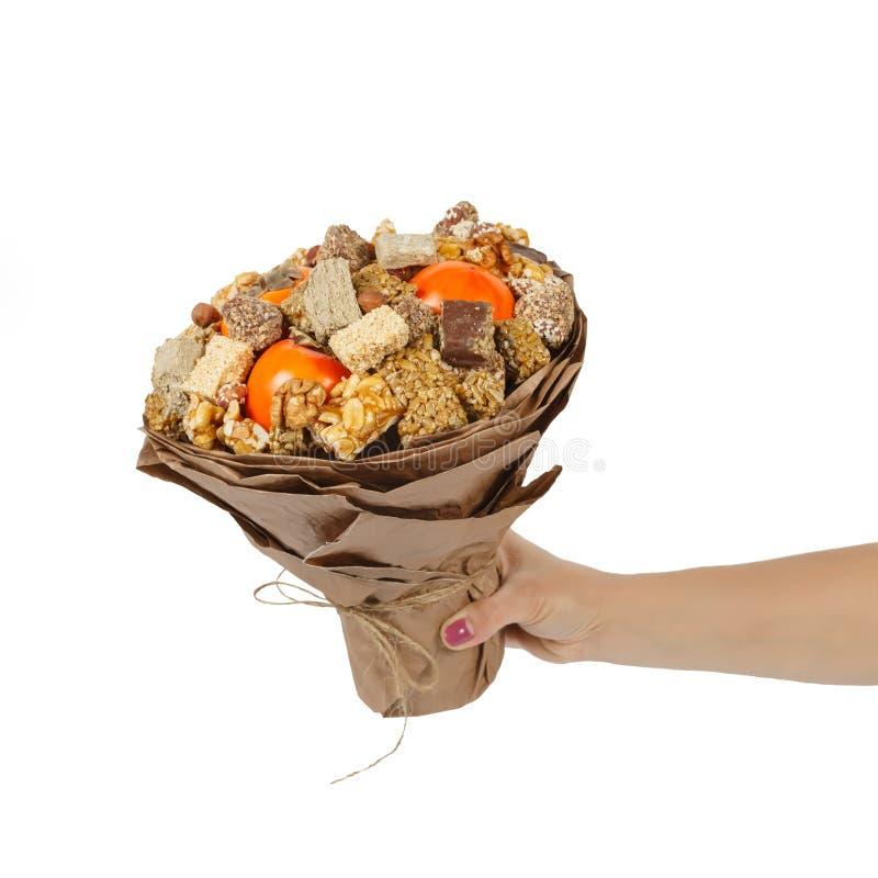 De vrouwelijke hand houdt een origineel boeket bestaand uit oosterse snoepjes - halva, sesambreuken, noten, chocolade en dadelpru stock foto