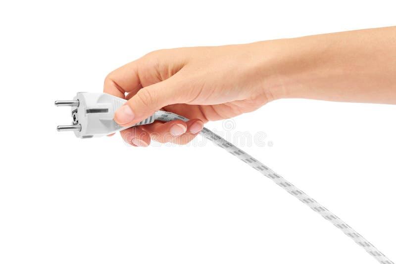 De vrouwelijke hand houdt elektrische die kabel met stop op een witte achtergrond wordt geïsoleerd stock foto